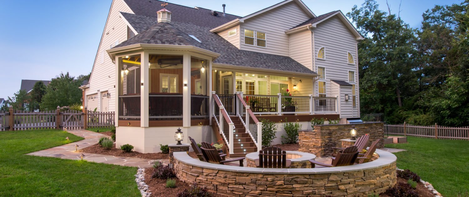 white house with large outdoor living space and landscaping
